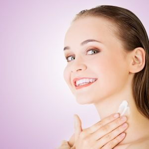 woman putting skin cream on her neck